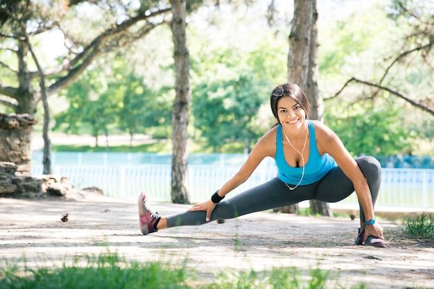 Femme de remise en forme faisant des exercices d'étirement dans le parc