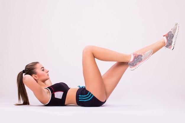 Femme de remise en forme faisant des exercices d'étirement. tourné sur toute la longueur de la jeune femme isolée sur fond blanc.