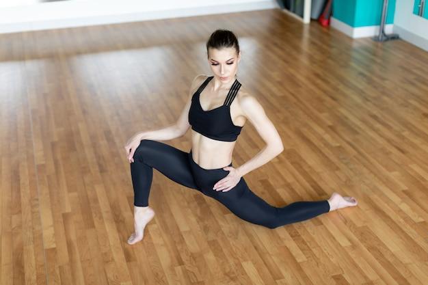 Femme de remise en forme faisant des exercices de fentes pour l'entraînement musculaire des jambes. fille active faisant un exercice de fente avant une jambe avant pour les fesses.