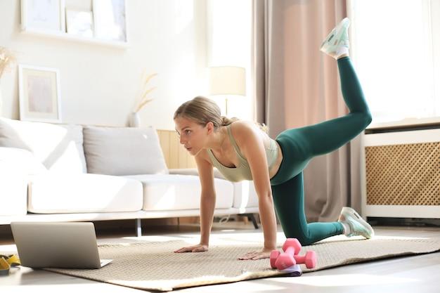 Femme de remise en forme faisant des exercices de sport et regardant des tutoriels en ligne sur un ordinateur portable, s'entraînant dans le salon. restez à la maison activités.