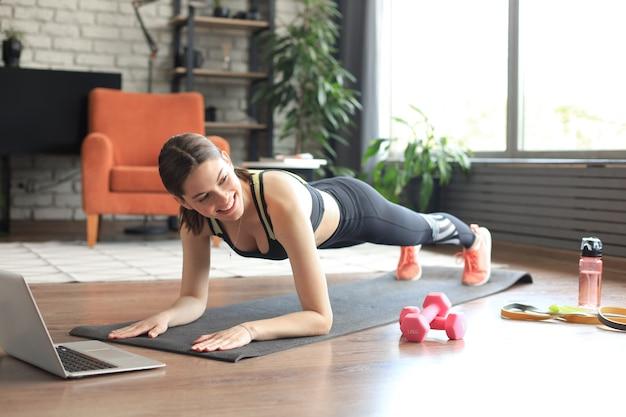 Femme de remise en forme faisant de la planche et regardant des tutoriels en ligne sur un ordinateur portable, s'entraînant dans le salon. restez à la maison activités. vue de dessus.