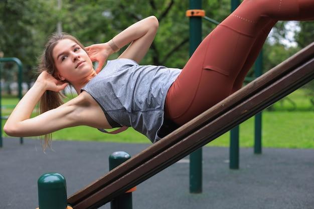 Femme de remise en forme faisant des redressements assis dans une salle de sport en plein air se réveillant en musculation.