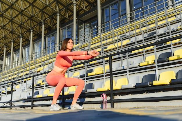 Femme de remise en forme faisant des redressements assis dans le stade de l'entraînement. fille sportive exerçant les abdominaux, en plein air