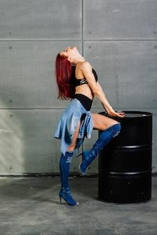 Femme de remise en forme sur fond de béton de ciment près d'un baril noir