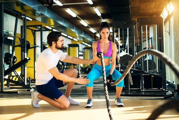 Femme de remise en forme en formation faisant des exercices avec une corde de combat dans la salle de gym avec un entraîneur à côté d'elle.