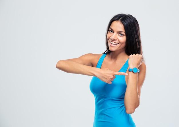 Femme de remise en forme heureuse pointant sur le tracker de fitness