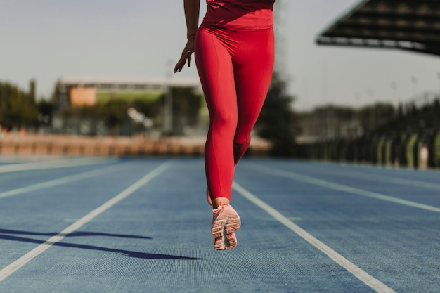 Femme de remise en forme méconnaissable sur le stade en cours d'exécution par les pistes bleues