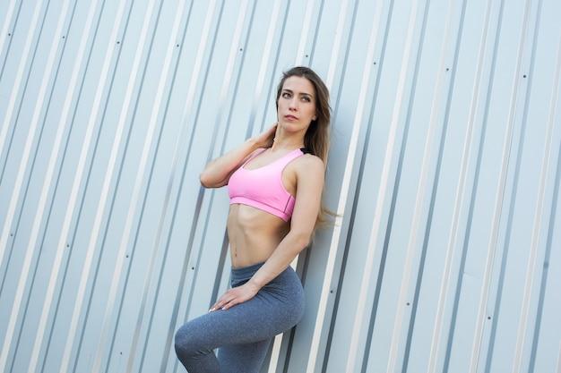 Femme de remise en forme posant sur fond de mur