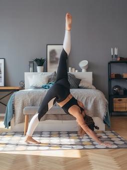 Femme de remise en forme pratiquant le yoga à la maison, elle fait des exercices d'étirement de flexion avant.