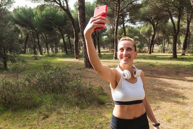 Femme de remise en forme prenant une photo ou un selfie avec son smartphone pour les médias sociaux tout en faisant une séance d'entraînement. mode de vie sain.