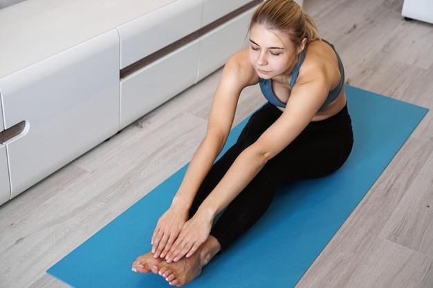 Femme de remise en forme qui s'étend des jambes assis sur le sol à la maison