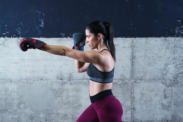 Femme de remise en forme sexy forte sur la formation de boxe