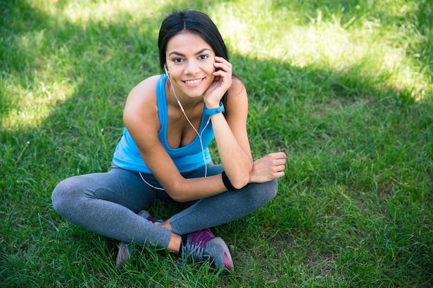 Femme de remise en forme souriante assise sur l'herbe verte