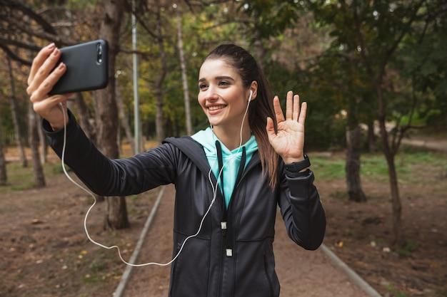 Femme De Remise En Forme Souriante, écouter De La Musique Avec Des écouteurs, Prendre Un Selfie En Se Tenant Debout Dans Le Parc Photo Premium