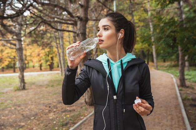 Femme de remise en forme souriante, écouter de la musique avec des écouteurs, tenant une bouteille d'eau en se tenant debout dans le parc