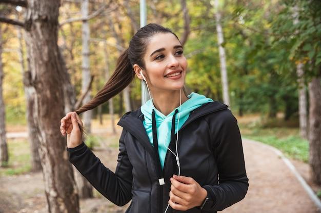 Femme de remise en forme souriante, écouter de la musique avec des écouteurs, tenant un téléphone mobile en se tenant debout dans le parc