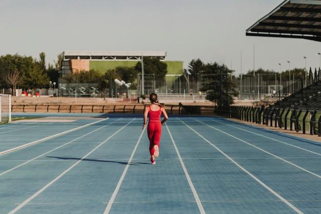 Femme de remise en forme sur le stade en cours d'exécution par les pistes bleues