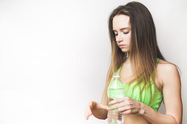 Femme de remise en forme en t-shirt vert et aux cheveux longs boit de l'eau