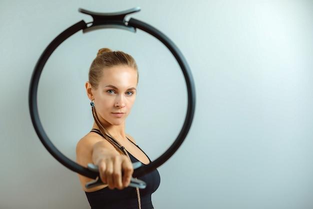 Femme de remise en forme tenant un anneau de remise en forme, surface grise