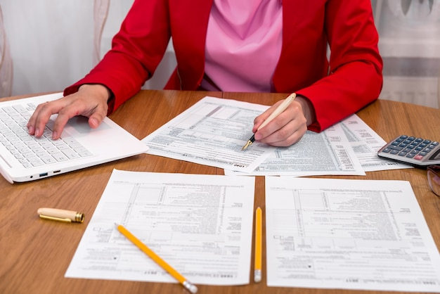 Femme remplissant le formulaire 1040 et en tapant sur un ordinateur portable