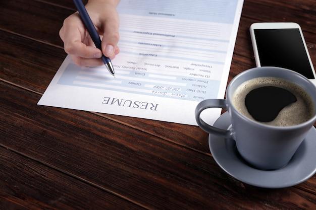 Femme remplissant le formulaire de cv sur table en bois, gros plan