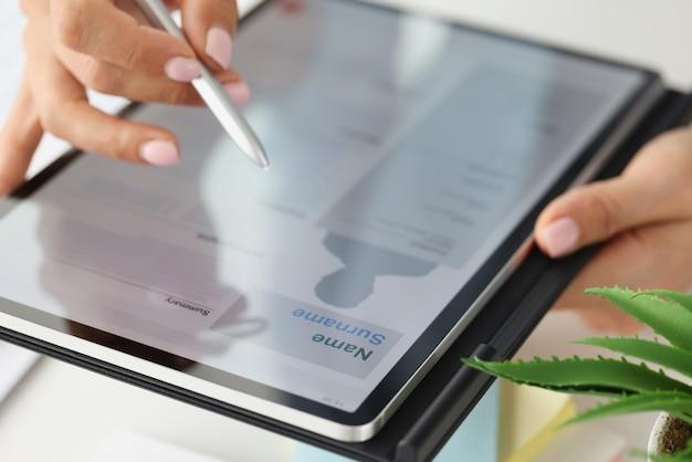 Une femme remplit un formulaire de cv électronique sur une tablette pour trouver un emploi