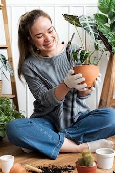 Femme rempotant une plante d'intérieur à l'intérieur de sa maison