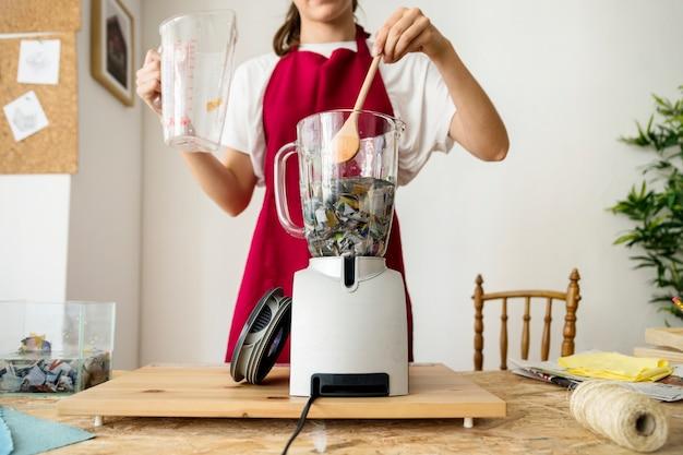 Femme en remuant le papier déchiré dans un mélangeur
