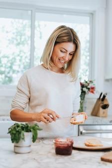 Femme répandant du fromage à la crème végétalien sur un toast
