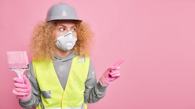 Femme réparatrice ou peintre indique loin sur l'espace de copie tient un pinceau occupé à faire des rénovations de maison porte un casque de protection respiratoire et un uniforme