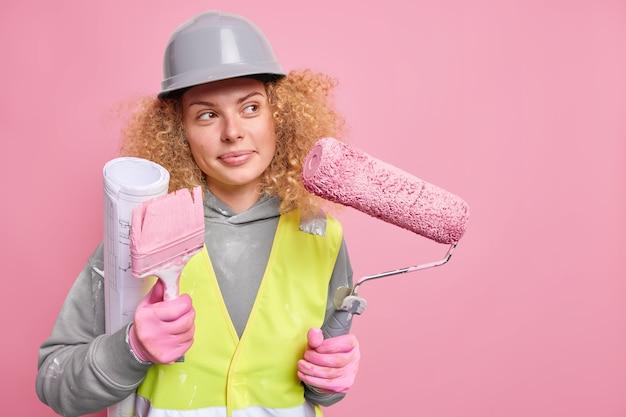 Femme réparatrice pense à la conception de la maison porte un rouleau de plan et une brosse vêtue de vêtements de travail