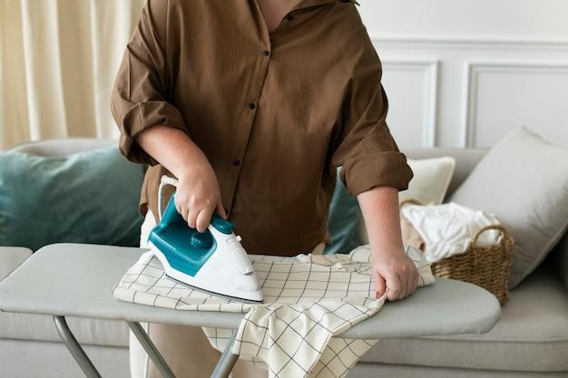 Femme repassant une chemise les tâches ménagères de blanchisserie