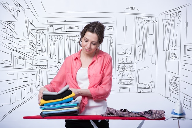 Femme repassant des vêtements dans sa chambre