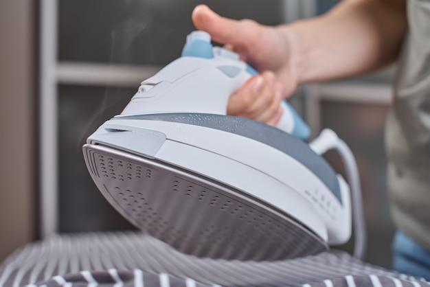 Femme, repasser des vêtements avec un fer moderne