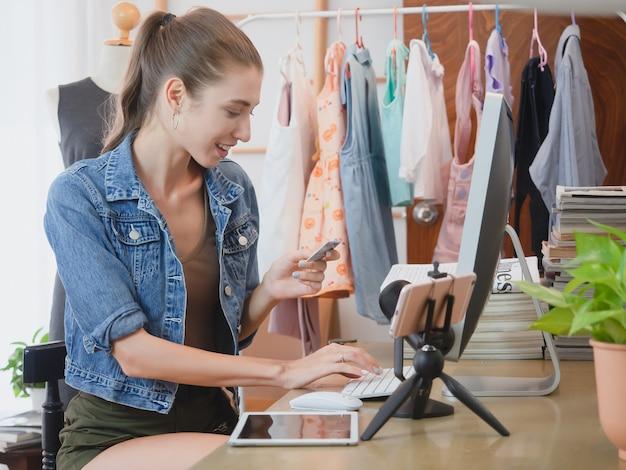 Une femme répond aux questions des clients par le biais de son ordinateur sur la vente en ligne, une fille faisant des affaires chez elle