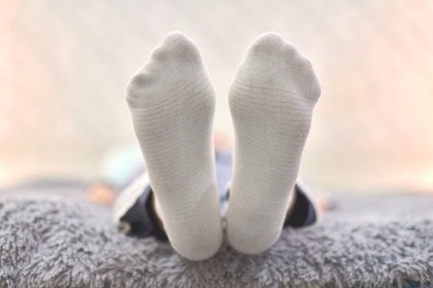 Femme reposant sur un canapé dans des chaussettes douces et confortables.