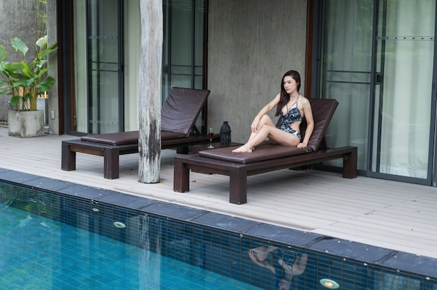 Femme reposante sur une chaise à la piscine