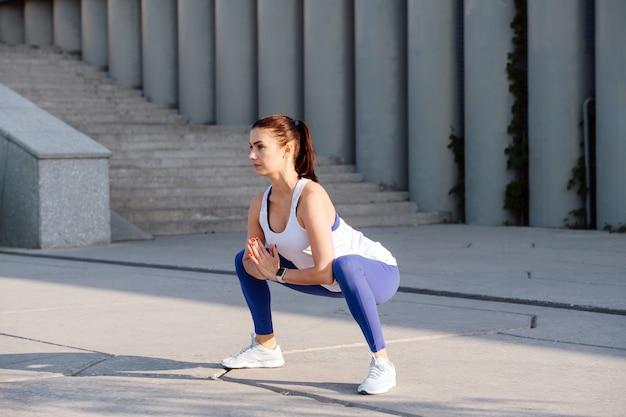 Femme résolue travaillant dans la rue faisant des squats