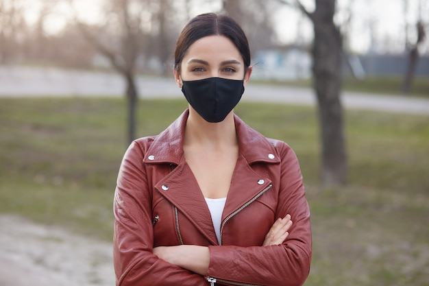 Femme respirant de l'air frais dans des endroits pauvres, portant une élégante veste en cuir et un masque contre la grippe