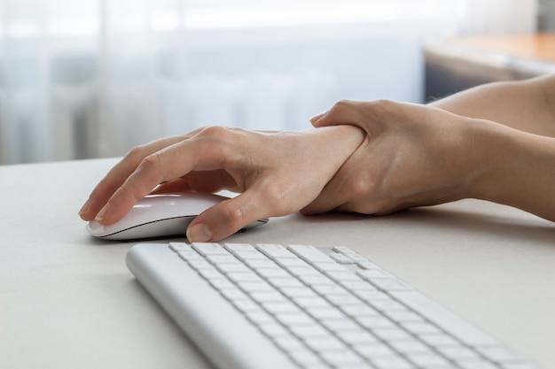 Une femme ressent une douleur au poignet avec sa souris d'ordinateur.