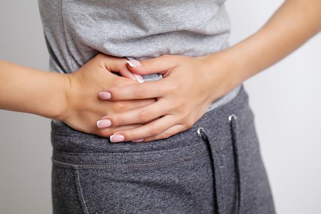 La femme ressent une douleur dans l'abdomen, tenant le lieu de la douleur avec ses mains