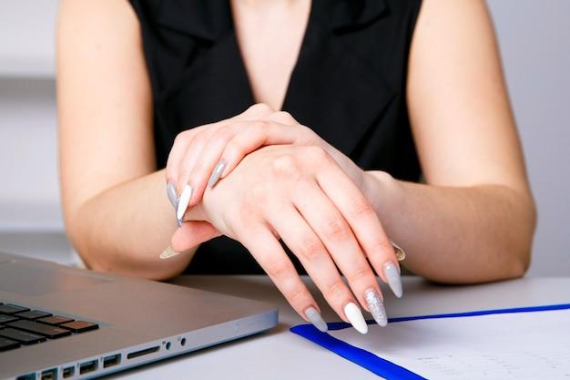 Femme ressentant une douleur au poignet après avoir travaillé sur un ordinateur portable.