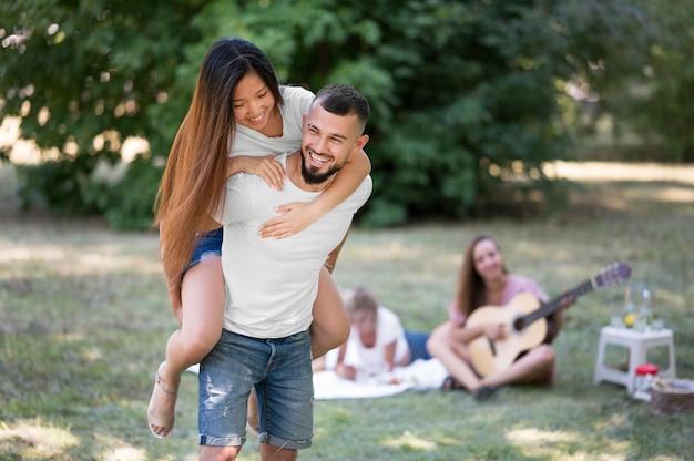 Femme restant sur le dos de l'homme à l'extérieur