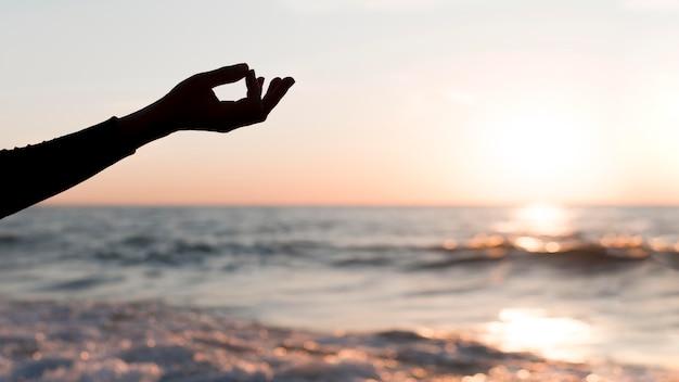 Femme restant avec son bras à côté d'elle au coucher du soleil avec copie espace