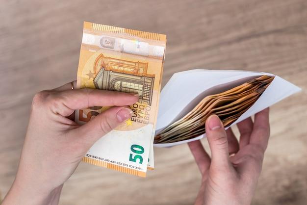 Femme retirant de l'argent en euros d'une enveloppe