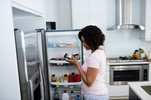 Femme retirant la bouteille du réfrigérateur dans la cuisine