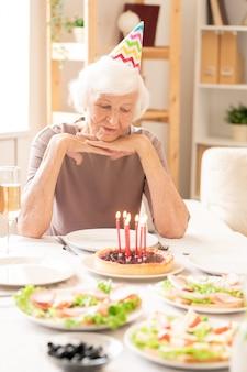 Femme à La Retraite âgée à La Recherche De Bougies Allumées Sur Un Gâteau Fait Maison Alors Qu'il était Assis Par Table D'anniversaire Servi Photo Premium