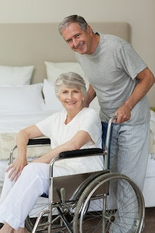 Femme à la retraite dans son fauteuil roulant avec son mari