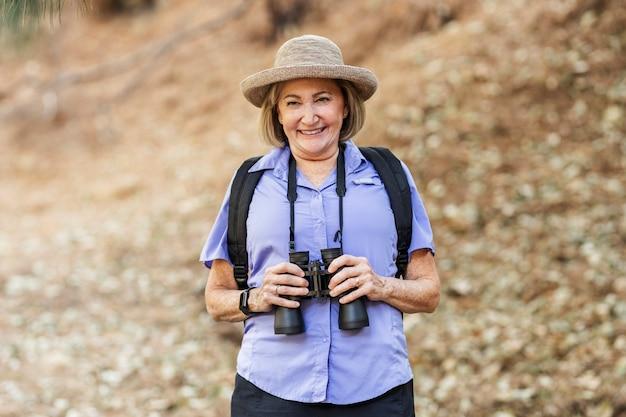 Femme à la retraite avec des jumelles dans la forêt