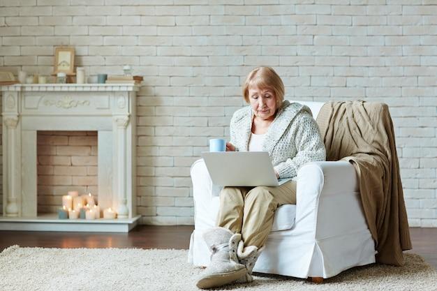 Une femme retraitée s'installe dans un fauteuil